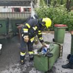 Feuerwehrmann mit ausgebrannten Mülleimer